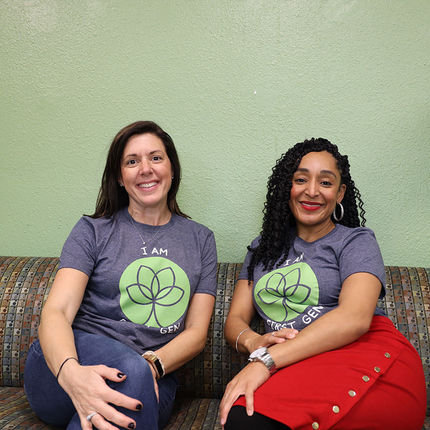 Robyn Centilli (right), assistant director of the Office of Student Enrichment, sits with Consuela Howell, the director of the Office of Student Enrichment. Both are wearing their FLI Week shirts.