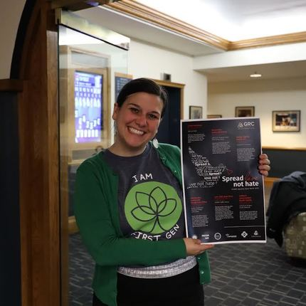 Sara Agostinelli, assistant director for LGBTQ initiatives and administration at the GRC, holds a flyer for events during StaND Against Hate Week while wearing her FLI T-shirt.