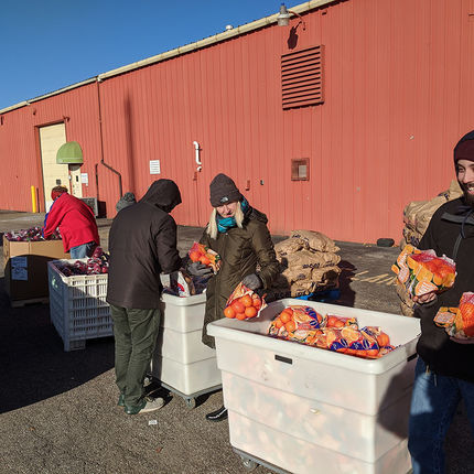 Jenn Lechtanski, graphic designer; Grant Osborn, assistant director; Anna Dolezal, student programs assistant manager; and Connor Bran, communications and publications coordinator, gather food for families.