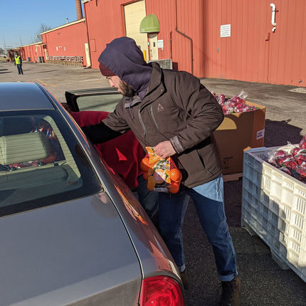 Connor Bran, communications and publications coordinator, helps load a car.