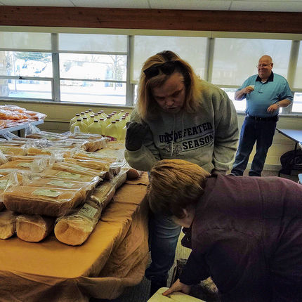 In the center, helping pack a bag of food, is Donna Thompson (change management professional, OIT).