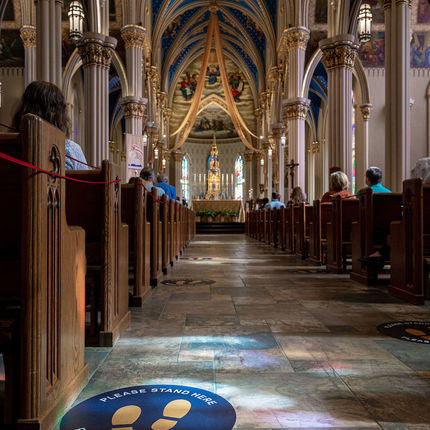 Signs on the floor of the Basilica of the Sacred Heart remind Mass attendees of physical distance guidelines in place due to coronavirus. (Photo by Matt Cashore/University of Notre Dame)