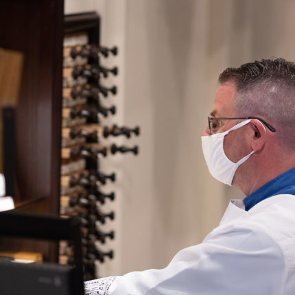 Andrew McShane plays the organ wearing a mask at the first Sunday Mass held at the Basilica since it was closed to the public in March. (Photo by Matt Cashore/University of Notre Dame)