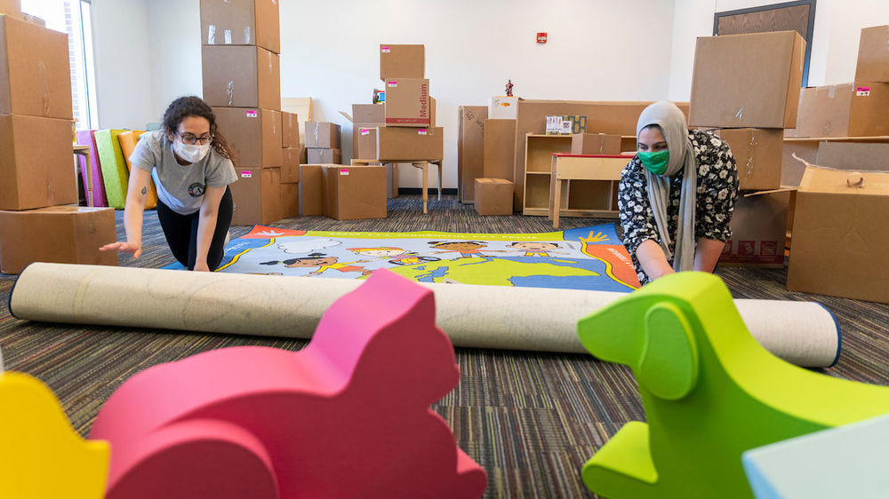 Celine Marcos and Samantha Musleh roll out a rug at the new Robinson Community Learning Center (RCLC) in South Bend. (Photo by Barbara Johnston/University of Notre Dame)