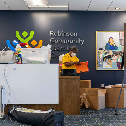 Lu Ella Webster, adult programs coordinator, unpacks boxes behind the reception desk at the new Robinson Community Learning Center (RCLC) in South Bend. (Photo by Barbara Johnston/University of Notre Dame)