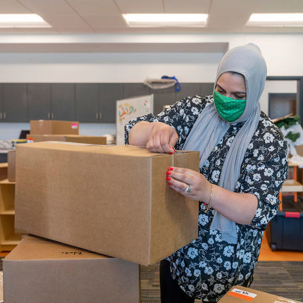 Samantha Musleh unpacks boxes at the new Robinson Community Learning Center (RCLC) in South Bend. (Photo by Barbara Johnston/University of Notre Dame)