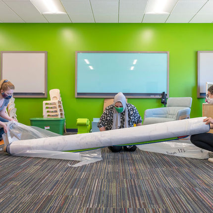 Abigail Amat, Samantha Musleh and Celine Marcos roll out a rug at the new Robinson Community Learning Center (RCLC) in South Bend. (Photo by Barbara Johnston/University of Notre Dame)
