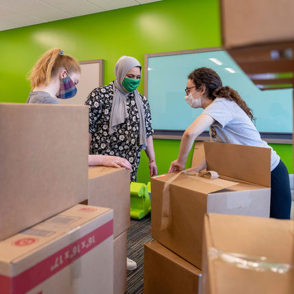 Abigail Amat, Samantha Musleh and Celine Marcos unpack boxes at the new Robinson Community Learning Center (RCLC) in South Bend. (Photo by Barbara Johnston/University of Notre Dame)