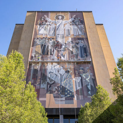"Workers from C&S Masonry Restoration, LLC, (names left-right) Kenny Allgower, Bryan Gundlach and Steve Bryan do preventive maintenance on the ""Word of Life"" mural on the south side of the Hesburgh Library. (Photo by Barbara Johnston/University of Notre Dame)"