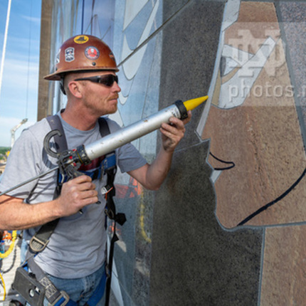 "Steve Bryan from C&S Masonry Restoration, LLC, does preventive maintenance on the ""Word of Life"" mural on the south side of the Hesburgh Library. (Photo by Barbara Johnston/University of Notre Dame)"