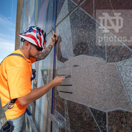 "Bryan Gundlach from C&S Masonry Restoration, LLC, does preventive maintenance on the ""Word of Life"" mural on the south side of the Hesburgh Library. (Photo by Barbara Johnston/University of Notre Dame)"