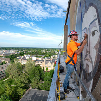 "Bryan Gundlach from C&S Masonry Restoration, LLC, does preventive maintenance on the ""Word of Life"" mural on the south side of Hesburgh Library. (Photo by Barbara Johnston/University of Notre Dame)"