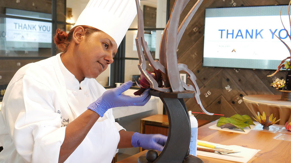 Executive Pastry Chef Sinai Vespie puts the final touches on a chocolate sculpture at a special event held at the University.