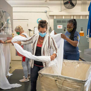 Jessica Jordan, production manager, (front center) helps Karen Fulford (right) and Karen Qureshi iron table linens at St. Michael's Laundry. (Photo by Barbara Johnston/University of Notre Dame)