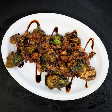Fried Brussels is an appetizer with zing! The fried Brussels sprouts are tossed with bacon, spiced nuts, and a Vietnamese vinaigrette.