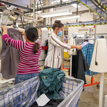 Jessica Jordan, production manager, (right) helps Rosita Tucubal at the shirt press station at St. Michael's Laundry. (Photo by Barbara Johnston/University of Notre Dame)