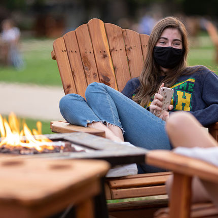 A student chats with friends on South Lawn Commons. Photo by Matt Cashore/University of Notre Dame.